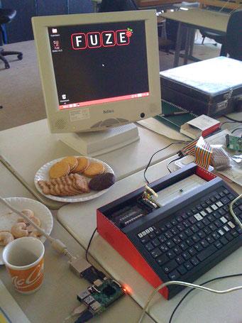 Bildschirm mit Fuze-Logo, Fuze-Box mit Tastatur, Kekse, Becher