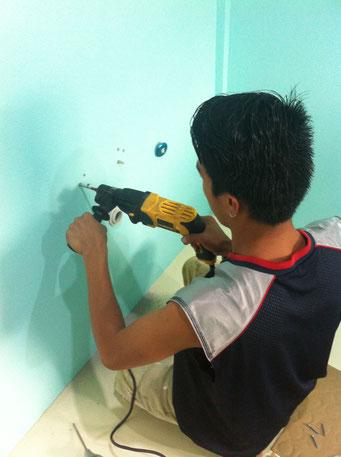 Ein mann bohrt löcher in die Wand