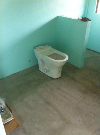 Wc schüssel steht auf boden, im Hintergrund blaue Wand