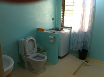 Waschmaschine und Wc auf gelbem Boden, im Hintergrund blaue Wände
