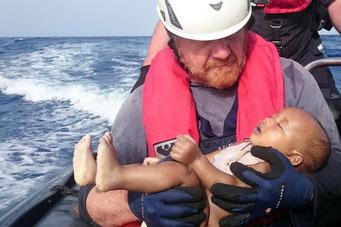 Ein Helfer der deutschen Seenotrettung Sea-Watch hält ein Baby in seinen Armen. Das Kind ist tot, ertrunken im Mittelmeer. (Foto: Christian Buttner | Eikon Nord GmbH Germany)
