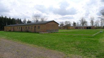Ansicht der ehemaligen Latrine (linke) und der ehemaligen Küche (hinten). Rechts ist der Grundriss einer nicht mehr vorhandenen Baracke markiert. Foto: Andreas Ehresmann, 30.4.2013