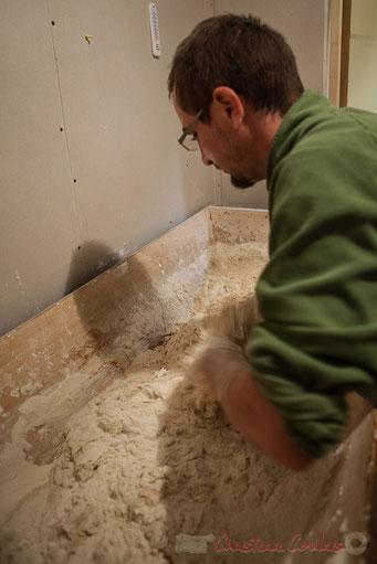 Pétrissage manuel dans une maie à farine