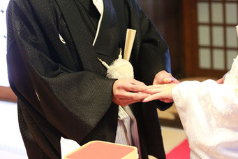 山梨県武田神社結婚式神殿にて指輪の交換シーンです 新郎から新婦え指輪をはめるシーンです