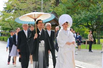 山梨県武田神社結婚式神殿に向かうシーンの写真です 新郎新婦の表情が和やかです