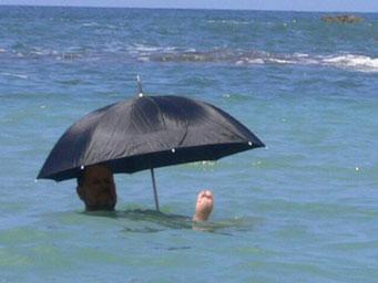 Mann mit Regenschirm beim Baden
