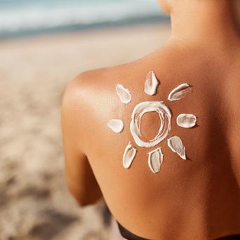 Sonne auf Frauenschulter am Strand - Solarenergie