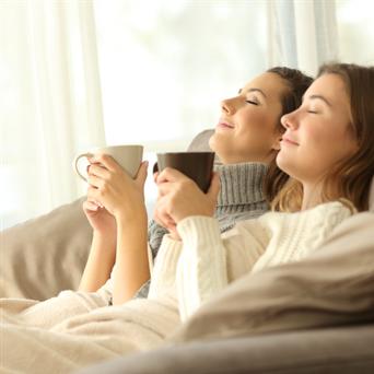 Zwei Frauen mit Kaffe gemütlich auf der Couch - Moderne Brennwert-Heizungen