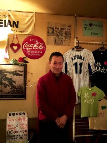 店主の飯田さん。店内にはアルバイトをしていた東投手(横浜DeNA)のユニフォームなどが