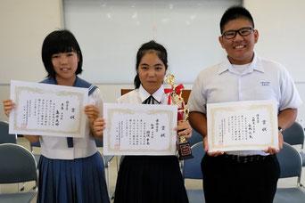 最優秀賞の狩俣さん(中央)、優秀賞の島仲さん(左)、金城君(右)=16日午後、八重山合同庁舎