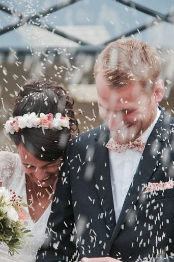 Mariée avec couronne de fleurs assortie au la boutonnière de son époux à la sortie de l'église. Jeté de riz à la sortie de l'eglise. Blog La cinquieme saison.