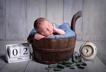 BabyfotografBaby liegt neben Wecker in einem Korb