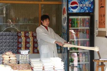"""Ein typischer Touristen-Snack in Suzhou. Zucker wird erhitzt und mit Sesam, Erdnüssen und Mehl gemischt. Es gibt verschiedene Rezepte. Das """"Mischen"""" geschieht wie hier gezeigt durch Drehen und Ziehen."""
