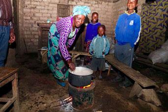 Klimaneutral Reisen - Klimaprojekt Ruanda: Familie mit Feuerstelle