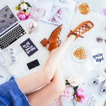 Frauenbeine mit Schuhe Laptop Kopfhörer Zeitschrift