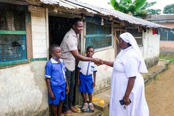 Schwester Irene bringt nach dem Unterricht die Schüler John Adawan und John Adu zu ihrem Vater John Baidoo nach Hause. pde-Foto: Fritz Stark/missio