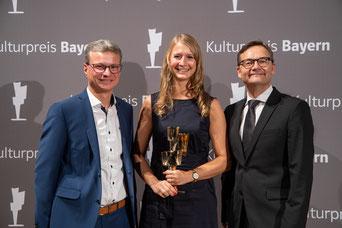 Die Neumarkterin Dr. Tanja Kurzendorfer (Mitte) erhält den Kulturpreis Bayern 2019 als beste Absolventin der Friedrich-Alexander-Universität Erlangen-Nürnberg. Überreicht wurde der Preis von Reimund Gotzel, Vorstandsvorsitzender der Bayernwerk AG (rechts)