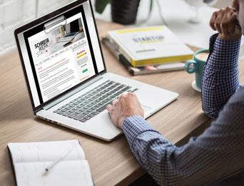 Mann vor dem PC, der die Website der Schreibwerkstatt anschaut