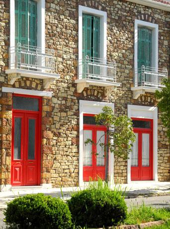 Steingebäude Fensterläden rot und blau