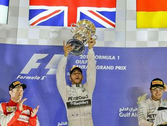 Lewis Hamilton (M) holte sich in Bahrain den Sieg vor Kimi Räikönnen (l) und seinem Teamkollegen Nico Rosberg. Foto: Srdjan Suki