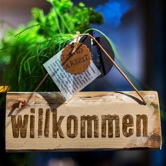 """Holzschild mit Aufschrift """"Willkommen"""", am Lederband hängend mit einem Etikett """"Handarbeit"""""""