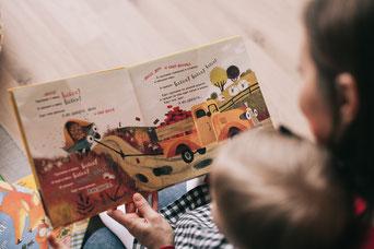 Foto: Frau liest einem Kind ein Buch vor