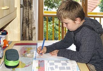 Foto: Schulkind erledigt Hausaufgaben