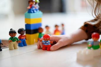 Foto: Kind spielt mit Spielzeugfiguren