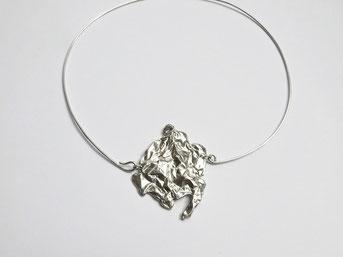 Un pendentif au motif froissé en argent fixé à un tour du cou est placé sur fond blanc.