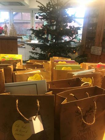 Im Hüder Dorfhaus stehen unzählige, prall gefüllte Nikolaustüten aus Papier. Im Hintergrund steht ein Weihnachtsbaum.