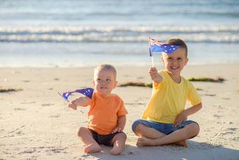 ビーチでオーストラリアの旗を振る子供たち