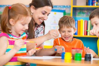 子供たちとお絵かきするチャイルドケアスタッフ