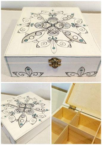 Boîte en bois avec 9 compartiments pouvant servir de boite à thé peinte en blanc sur le dessus un dessin mandala fait à l'encre de chine noire et quelques points de couleur bleu vert