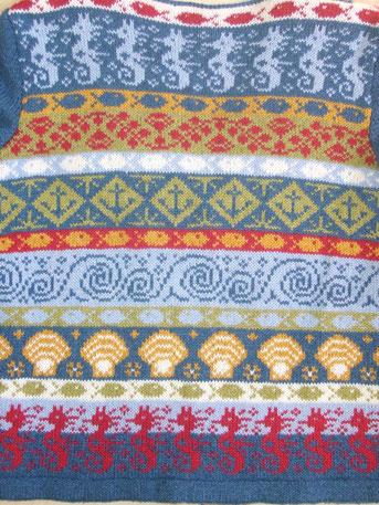 Rückseite einer Jacke mit eingestrickten Seepferdchen, Muscheln, Wellen, Anker , Fische und Wasserpflanzen in den Farben Jeansblau, Hellblau, Wollweiß, Gelb, Hellgrün und Rot