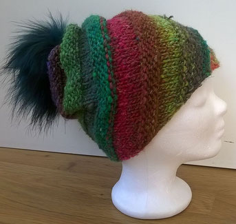 schräg gestrickte Mütze in bunt mit einem Fellbommel in Grün