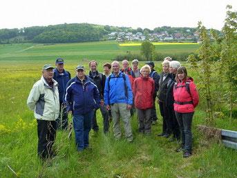 Im Vordergrund die Teilnehmerinnen und Teilnehmer (links Wanderführer Dr. Erwin Günther). Im Hintergrund der Büddenteich (heute Goldhäuser Teich), ganz oben der Ort Goldhausen.