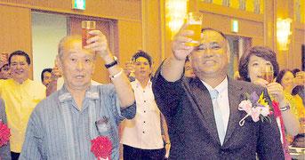 就任2周年激励会で乾杯する砂川県議(右)と仲井真知事(14日夜)