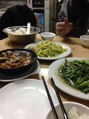 Unser Abendessen. Zwei Personen. Vorne rechts gedünstete Spargelblätter, im Hintergrund gedünstete Bittermelone, vorne links Auberginen-Gulasch