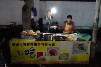 Die Bäckerei besteht aus einem Handwagen, der so groß wie ein Tapeziertisch ist. Links auf dem Foto ist der Deckel des Kohleofens zu erkenne, auf dem die fertigen Brote warmgehalten werden.