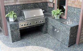 Pebbles in an exterior kitchen, covering the floor, sides of the counters, and backsplash behind a built-in barbecue grill