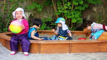 Die Kinder spielen in der Sandkiste