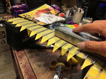ギターネックの上からステンレスフレットをやすりがけしている作業