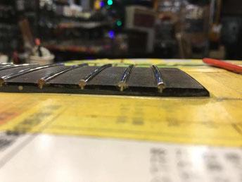新しいステンスフレットがついたギターネックを横から見た画像