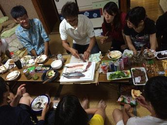 気仙沼ゲストハウスにて地元の方がサンマの捌き方を学生に教える様子。