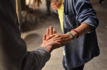 Zwei Menschen reichen ahnender die Hand