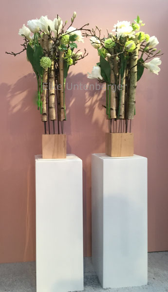 zwei große weiße Podeste mit ausgefallener Dekoration aus Birkenästen und weißen Seidenblüten