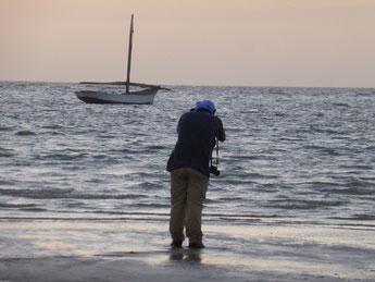 Un homme de dos, les pieds dans l'eau qui photographie une barque (lanche.