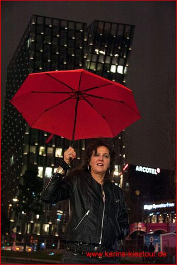 Karin steht mit aufgespanntem Regenschirm vor den Tanzenden Türmen auf der Reeperbahn.
