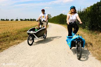 Personen auf verschiedenen Lasten e-Bike fahren durch die Felder