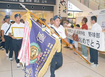 優勝旗を掲げ帰島した八重山高校野球部のメンバー=12日夜、石垣空港